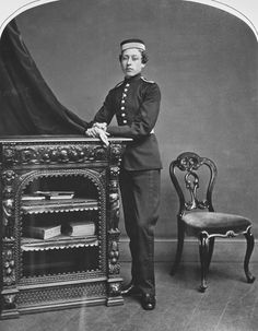Full length of P. Arthur standing, both hands on the top of a carved chest w. open shelving, on which some books. He wears cadets uniform, inc. He holds his gloves. Drapery b& l., a chair to r. Top corners of photograph are rounded.