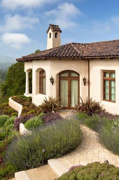 Love this serene, Mediterranean-influenced home exterior and lavender planted garden landscaping.