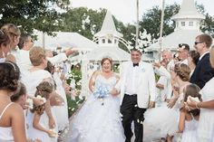 Bride and groom exit their Disney Fairy Tale Wedding ceremony to a petal toss from their guests at Disney's Wedding Pavilion