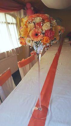 Magas esküvői asztaldísz martinis vázában narancs árnyalatokban. Neked is szívesen készítünk hasonlót: https://eskuvoidekor.com/viragdekoracio