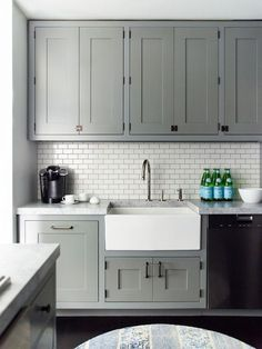 Gray recessed panel cabinets, white subway tile backsplash with gray grout, apron sink, and dark hardwood floors.