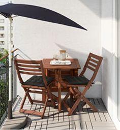 Et altanbord med to stole på en solbeskinnet altan