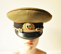 This is an original Bulgarian Peoples Army artillery / armoured troops officers service uniform visor cap. It has an authentic enamel cockade with the red star, three colours and the lion. This hat dates back to the Soviet Era and was used from 1950s to 1970s.  It has been used a lot and shows signs of wear and age but still preserves its amazing character. Its a fantastic movie & stage prop as well as a great historical piece from the Cold War! - - - - - - - - - - - - - - - - - - - ...