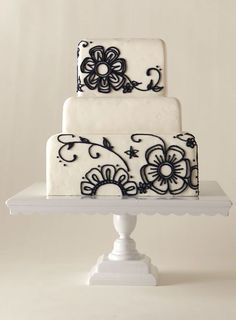 Simple white layered cake with black floral piped details