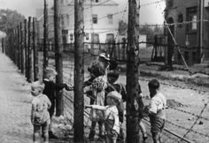 Two Dutch children passing food to German children through the fence that divided the streets of Nieuwstraat/Neustraße, Kerkrade 10 October 1946