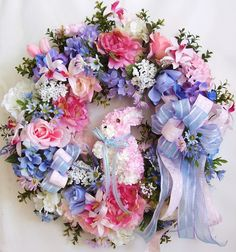 """This beautiful Pink Light Green Easter flower door wreath sets on a green styrofoam wreath base.    The wreath is embellished with lots of greenery, beautiful pink roses, spring pink/white Hydrangea, pink peony , light blue roses and hydrangea, and light blue/pink daisy. The wreath accented with a lovely Raz pink Hydrangea Easter Bunny. I finish the wreath with a pink and light blue ribbon bow.     The wreath measures from tip to tip at 25"""" (L) x 25"""" (W) x 7.5""""(D)."""