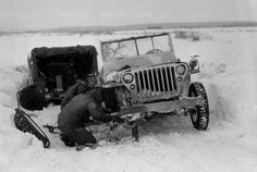Two U.S. 99th Infantry Division GIs work to change a tire and repair their Jeep in the snow near Elsenborn, Belgium, 27 January 1945.