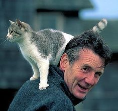 Cat on Michael Palin's shoulder - and may I say - it is obvious (look at the the spreaded whiskers and the raised tail) that the cat loves him <3