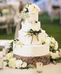 White rustic wedding cake on tree slab