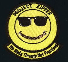 """This patch represents an unknown project undertaken by the 413th Flight Test Squadron The zipper seems to refer to the fact that the project cannot be discussed. The first part of the phrase """"We make threats"""" might refer to making simulated (or real) electronic """"threats"""" against aircraft."""