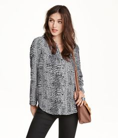 Straight-cut blouse in airy woven fabric. V-neck, buttons at front, two chest pockets, shoulder tabs with button, and long sleeves with roll-up tab and button. Slits at sides and slightly longer back section.