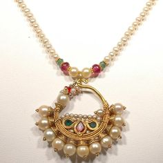 Freshwater pearl necklace with a pearl nose ring pendant in 22k gold.  The pendant is in excellent condition with very beautiful natural Basara pearls, rubies, and two green foil-backed emeralds. This would make an excellent addition to anyone's collection of traditional antique Indian jewelry or can be worn as a pendant with the use of a small jump ring.