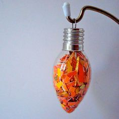 We love how fun this one is: take an old lightbulb, fill it with colorful scraps (or confetti), and voilà — you've got bright ornaments made easy.   Source: Etsy user rubyrockwell