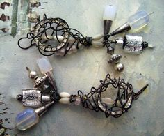 Trail of the Mermaid Tears: intentionally mismatched assemblage earrings anchored by vintage rhinestone wreaths, festooned by a cascade of shimmering moonstone beads, silver-foiled lampwork beads, mother of pearl beads, silver beads and cones adorned with a tangle of blackened wire - reminiscent of mermaids tears entangled in seaweed,   swirling endlessly in the oceans current.