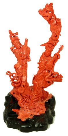 """CHINESE HAND CARVED RED CORAL MEIREN GROUP Large Chinese hand carved red coral group depicting two maidens holding sheng and pipa instruments. Phoenix and crane can also be seen. Rock form base with high relief flowers. Includes fitted wooden base. Measures 14 1/2"""" height x 7 1/2"""" width x 7"""" depth + 1"""" base height (36.8cm x 19.1cm x 17.8cm + 2.5 cm)."""