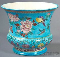 A Theodore Deck faience cachepot, France, circa 1875, polychrome enamel decorated with a blue ground and continuous panel of birds, insects and flowers over a band of flowers and scrolled foliage.