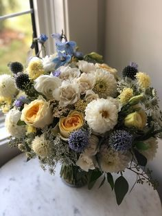 I love the soft colours in this wedding bouquet of white, pale yellow and soft blue! It features baby blue delphinium and globe thistle, yellow garden roses and lisianthus and white dahlias. #blueflower #yellowflower #blueandyellow #weddingcolorpalette #weddingcolorideas #blueweddingflowers #summerweddingbouquet #springweddingbouquet #dahliaseason #calgarywedding #calgary #calgaryflowers #flowersbyjanie