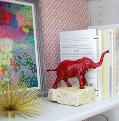 Spray painted plastic animals from the dollar store attached with super glue to several sample tiles from Lowes that are glued together. Easy bookend and cute. (Bronze spray paint)