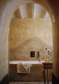 soft beige walls and cream towels and flowers.