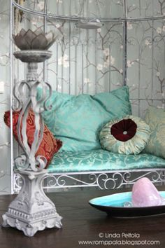 My livingroom with turquoise cushions, iron garden bench, cherry blossom wallpaper, lotus tealight, rustic candle holder