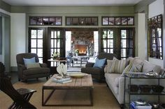 Beautiful craftsman family room with soft green walls with one full wall of French doors and transom windows in dark walnut frames.