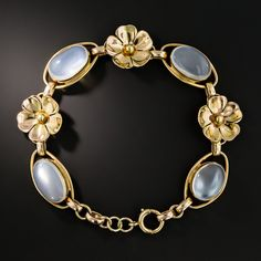 Four exceptionally lustrous oval moonstones glisten and glow from within bezel settings, bordered by elongated oval links and interspersed with a trio of golden flowers in this luminous wrist bauble hand-fabricated in gleaming 14K rosy-yellow gold and dating from the 1940s-50s. 7/16 by 7 inches.