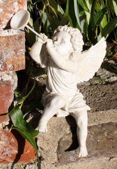 Sweet little cherub with trumpet sitting in the garden
