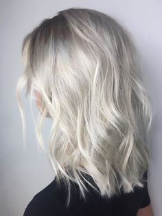 Medium length , platinum ice blonde with shadowed roots and lived in textured beach waves by @kaylen.o