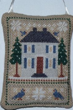 Cross stitch winter ornament with house.