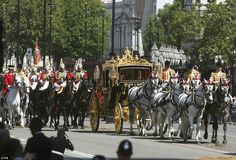 Journey: Her Majesty leaves the Palace in her gold coach surrounded by her guards on a glo...