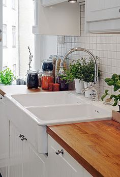 Ikea farmhouse sink, butchers block counters. Hides the cuts in the counter tops under the sink.