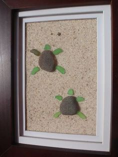 framed stone and seaglass turtles on sand. Use older frame with wood scrolls, shabby chic style.