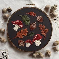 Acorns, mushrooms and autumnal leaves all make up this gorgeous embroidery hoop. #diy #craft