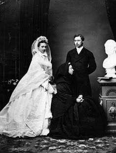 Wedding photo of Prince Albert Edward and Princess Alexandra of Denmark.  Queen Victoria is also in the photo wearing heavy mourning for her recently deceased husband.  Victoria stares resolutely at a bust of Prince Albert.  1863.