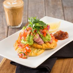 Two baked sweet corn and zucchini fritters topped with bacon, avocado…