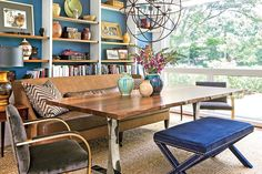 Casual Seating - 79 Stylish Dining Room Ideas - Southernliving. This space serves as a library/eating area. The room is casually arranged with a table, sofa, and bench pushed against the shelves.