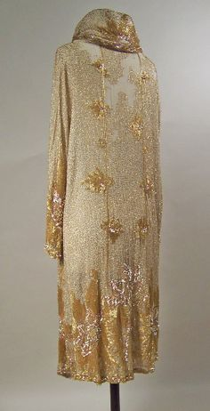 1925-28 evening coat, Ankle length evening coat with deep padded shawl collar, long sleeves and single clip fastening at neck. White cotton muslin, fully beaded over the whole ground in scattered gold bugle beads surrounding a stylised floral design in bugle beads, copper coloured pailettes and rhinestones. Pattern accentuates towards the hem and cuffs. The coat is exceptionally heavy. No label or lining.  Manchester Art Gallery