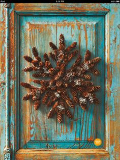 Pinecone Wreath with the weathered blue wood panel behind it is lovely!!