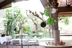 Kind of hard to see, but I love this idea as a centerpiece -- with little colourful cranes danging from the branches.
