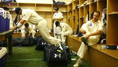 classic locker room and uniforms really quintessential scene. good composition with man doing stretches captures pre game tension