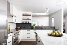 """The clean and modern kitchen is one of Baker's favorite rooms in the house. """"I love how the graphite penny-round backsplash really frames the view of the bay from the moment you walk in and complements the walnut accents,"""" she says.     The husband is an avid cook, so having a large and workable kitchen was a must. A deep single kitchen sink was high on the priority list, as were plenty of storage and counterspace."""