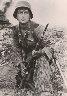 """A young SS-Sturmann of 3.SS-Panzer-Divison """"Totenkopf"""" waiting for the enemy on the outskirts of Warsaw in August 1944."""