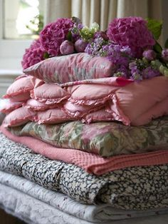 I LOVE bedding.  I have grown to LOVE flowers and all things classic feminine.  And this picture just speaks to my heart.  I love bed fluff and stacks of quilts!  Especially when they represent the love and handiwork of those who make them!
