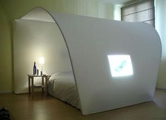 Minimal canopy bed doubles as screen for projection