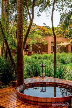 Módulos com diferentes atividades convergem para a piscina - Ofurô embutido. A tina (Kan Tui) foi instalada de forma a manter o paisagismo na altura do olhar de quem está imerso. Repare: o deck de cumaru circunda as árvores, que oferecem sombra. Projeto de Sandra Sayeg.