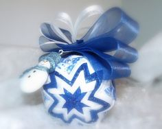 This ornament was inspired for someone very special in my life. it has deep blue shear glittered ribbon in the middle with a satin white ribbon and a shear ribbon with blue snowmen on it. attached is Blue shear ribbon and white ribbon with a Blue snowman attached to it. This ornament has been. This ornament will arrive gift boxed.  This one of two in this series.