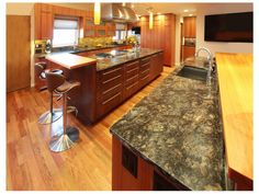 This spacious contemporary kitchen features gray granite countertops, custom cabinetry and a plasma TV. Ample countertop space provides plenty of room for food preparation, as well as a small breakfast bar that serves as the perfect space for casual dining.