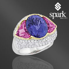 Mesmerize your senses with the extravagant violet-blue color of #tanzanite, surrounded by two stunning rubellites and encrusted with diamonds.  This #SparkCreations ring is a true one-of-a-kind piece, created to fascinate and be fascinated! Discover Spark Creations Jewelry at Liljenquist & Beckstead stores.