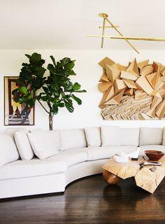 Sculptural wall art in neutral living room with modern light fixture