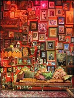 [L'art de l'accumulation.] Over the top red painted room covered in small picture frames, antique sofa, contrasting cushions
